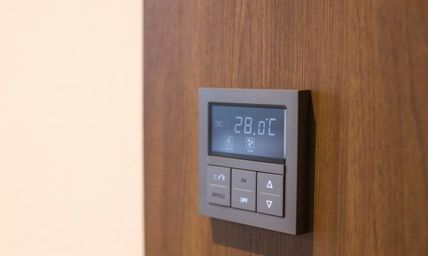 Airconditioning thermostat on a brown laminate wood cover wall