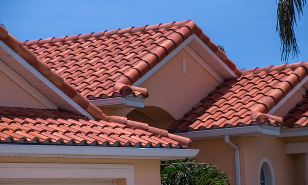 red ahingle roof on a suberban home with pink walls