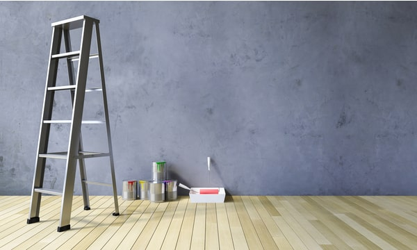 Grey Painted wall, light wood flooring, with ladder and paints
