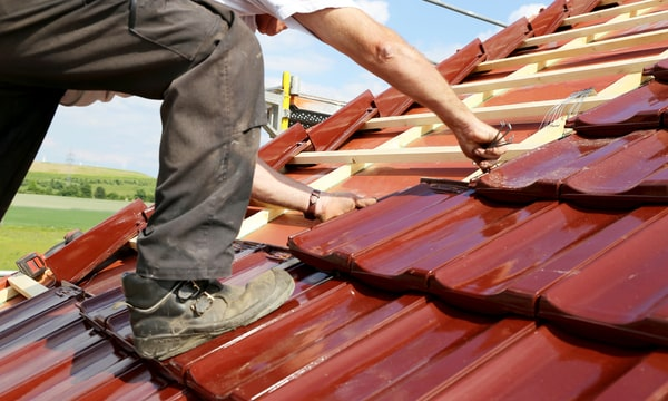 Roofer fixing red shingles on newly built roof