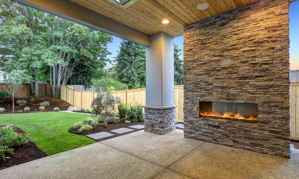 A fully renovated backyard with an electric fireplace, open porch, grass and greenery